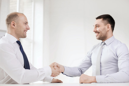happy customer: business and office concept - two smiling businessmen shaking hands in office