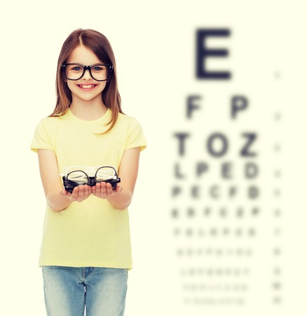 testing vision: people and vision concept - smiling cute little girl in black eyeglasses holding many glasses in her hands Stock Photo
