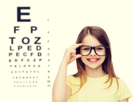 onderwijs, school en visie concept - lachend schattig klein meisje in zwarte bril