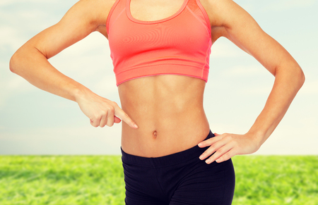 abdomens: fitness, exercise and diet concept - close up of woman pointing finger at her six pack Stock Photo