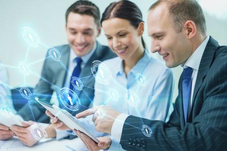 ビジネス、技術、接続、通信、人々 のコンセプト - タブレット pc コンピューターとオフィスでの議論を持つ仮想連絡先投影事業チームの笑顔