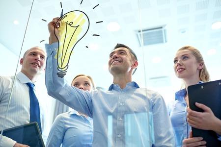 inspiracion: negocios, personas, trabajo en equipo y la planificaci�n concepto - sonriendo equipo de negocios con el marcador y la bombilla del doodle de trabajo en la oficina