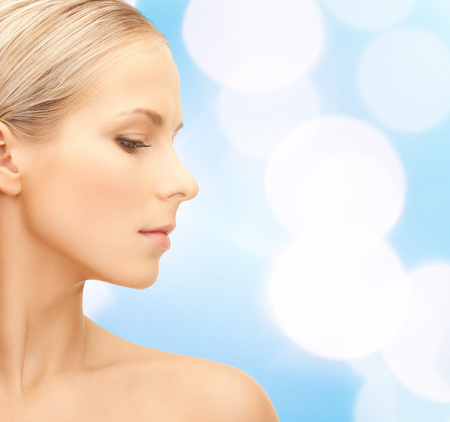 face side: beauty, people and health concept - beautiful young woman face over blue lights background