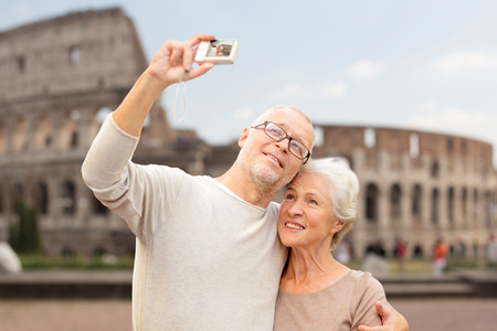 age, tourism, travel, technology and people concept - senior couple with camera taking selfie on street over coliseum background