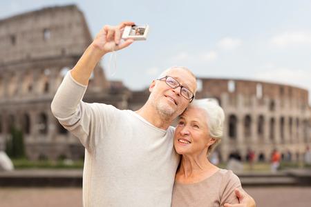 edad, turismo, viajes, tecnología y concepto de la gente - pareja senior con cámara que toma Autofoto en la calle más de fondo coliseo
