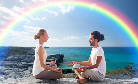 fitness, sport, people, yoga and lifestyle concept - happy couple meditating in lotus pose on summer beach photo