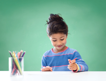 asian art: education, school, children, creativity and happy people concept - happy little girl drawing with coloring pencils over green chalk board background