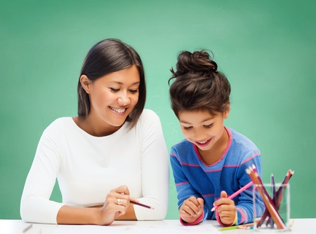 latin child: education, school, children, creativity and happy people concept - happy teacher and girl drawing over green chalk board background Stock Photo