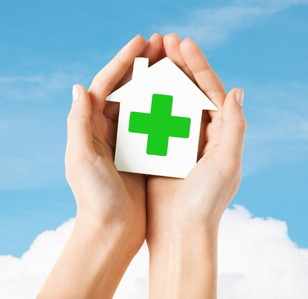 green cross: care, help, charity and people concept - close up of hands holding white paper house with green cross sign over blue sky and cloud background