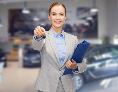 auto business, car sale, gesture and people concept - happy businesswoman or saleswoman with folder giving car key over auto show background Banco de Imagens