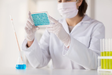 pharmacy technician: science, chemistry, biology, medicine and people concept - close up of young female scientist with pipette and flask making test or research in clinical laboratory Stock Photo