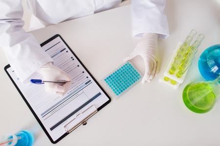 wetenschap, chemie, biologie, geneeskunde en mensen concept - close-up van wetenschapper met monster maken van onderzoek naar klinisch laboratorium Stockfoto