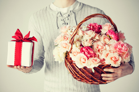 close up of man holding basket full of flowers and gift box. photo