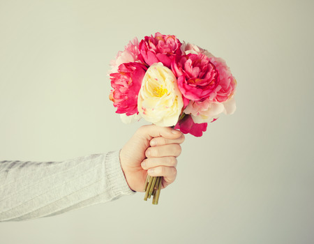 close up of mans hand giving bouquet of flowers.