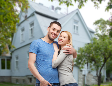 ownerships: love, people, real estate, home and family concept - smiling couple hugging over house background