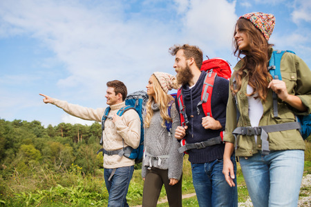hiking: adventure, travel, tourism, hike and people concept - group of smiling friends walking with backpacks Stock Photo