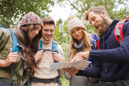forests: adventure, travel, tourism, hike and people concept - group of smiling friends with backpacks and map outdoors