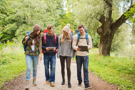 group cooperation: adventure, travel, tourism, hike and people concept - group of smiling friends with backpacks and tablet pc computer walking outdoors