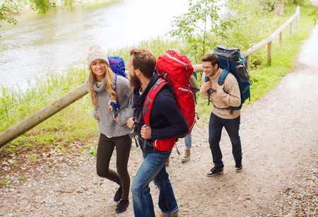 adventure, travel, tourism, hike and people concept - group of smiling friends walking with backpacks Stock Photo