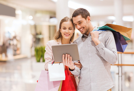 sale, consumerism, technology and people concept - happy young couple with shopping bags and tablet pc computer in mall
