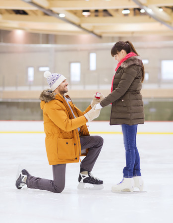 ice arena: people, love, proposal, sport and leisure concept - happy couple with engagement ring on skating rink Stock Photo