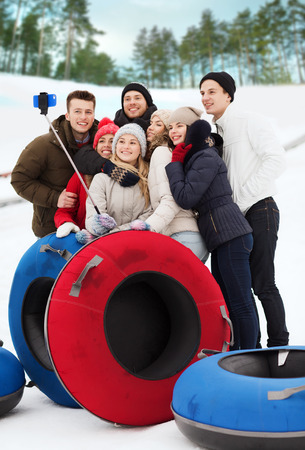 tubing: winter, leisure, sport, friendship and people concept - group of smiling friends with snow tubes taking picture by smartphone selfie stick outdoors