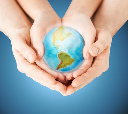 mundo manos: la gente, la geograf�a, la poblaci�n y la paz concepto - cerca de la mujer y las manos del hombre con el planeta tierra mostrando continente americano sobre fondo azul