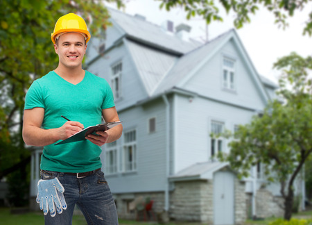 repair, construction, people, building and maintenance concept - smiling male manual worker in protective helmet taking notes to clipboard over house background