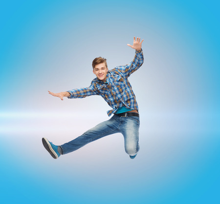 flying man: happiness, freedom, movement and people concept - smiling young man jumping in air over blue laser background