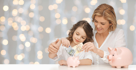 finance girl: people, finances, family budget and savings concept - happy mother and daughter with piggy banks and paper money over lights background