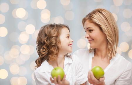 madre e hija adolescente: las personas, la familia, la alimentaci�n saludable y el concepto de la paternidad - feliz madre e hija con manzanas verdes sobre fondo las luces