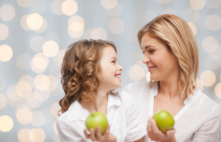 mother and teen daughter: people, family, healthy eating and parenting concept - happy mother and daughter with green apples over lights background
