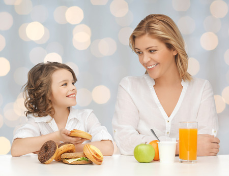 over eating: people, healthy lifestyle, family and unhealthy food concept - happy mother and daughter eating different food over holidays lights background