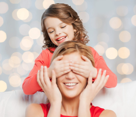 guess: people, happiness, leisure, family and motherhood concept - happy mother and daughter playing guess who game over holidays lights background