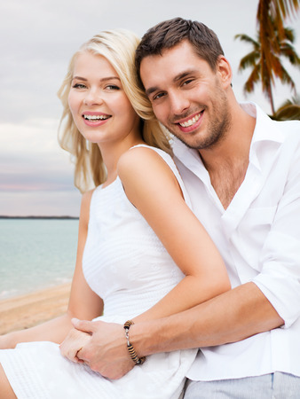 summer holiday, vacation, dating, travel and tourism concept - happy couple having fun and hugging over beach background photo