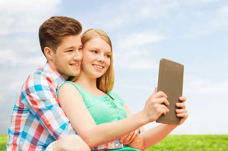 vacation, holidays, technology and love concept - smiling couple with tablet pc computer taking selfie over grass and blue sky background photo