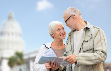 family, age, tourism, travel and people concept - happy senior couple with map over washington white house background photo
