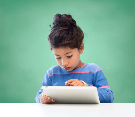 education, school, technology and children concept - little student girl with tablet pc over green chalk board background photo
