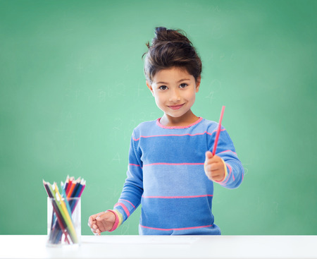 education, school, children, creativity and happy people concept - happy little girl drawing with coloring pencils over green chalk board background