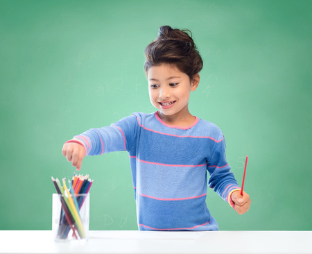 preteen asian: education, school, children, creativity and happy people concept - happy little girl drawing with coloring pencils over green chalk board background