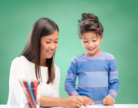 asian teacher: education, school, children, creativity and happy people concept - happy teacher and girl drawing over green chalk board background Stock Photo