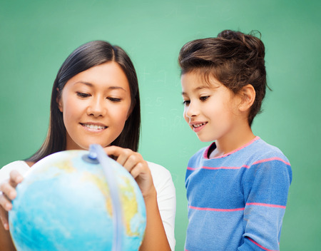 children, education, geography, school and happy people concept - happy teacher and girl with globe over green chalk board background photo