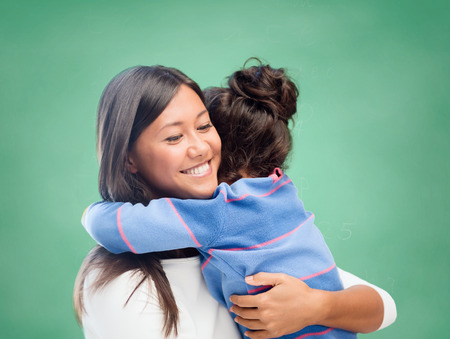 family, children, education, school and happy people concept - happy mother or teacher and little girl hugging over green chalk board background photo
