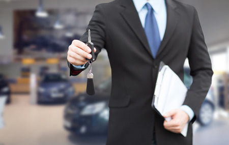 auto zaken, auto verkoop, gebaar en mensen concept - close-up van zakenman of verkoper met documenten geven van autosleutel op autoshow achtergrond Stockfoto