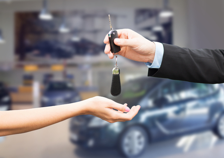 auto business, car sale, transportation, people and ownership concept - close up of car salesman giving key to new owner or customer over auto show background Stockfoto