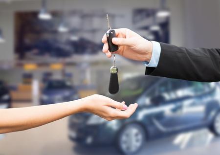 TRANSPORTE: negocio de autos, venta de los veh�culos, el transporte, la gente y concepto de propiedad - Cierre de vendedor de coches que da clave a nuevo propietario o cliente sobre Auto Show de fondo Foto de archivo