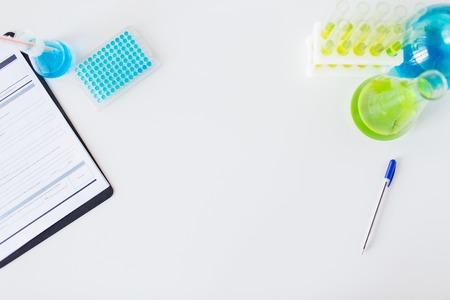 wetenschap, chemie, biologie, geneeskunde en reclame concept - close-up van het wetenschappelijk laboratorium tafel met spullen
