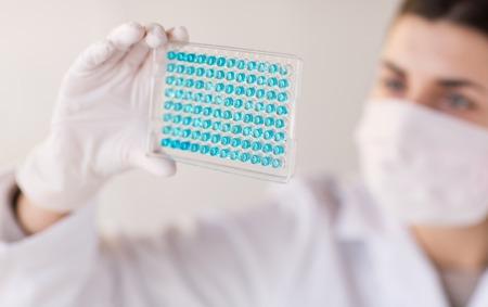 investigación: la ciencia, la qu�mica, la biolog�a, la medicina y la gente concepto - cerca de cient�fico de mujer joven con la prueba o investigaci�n pipeta y la toma de frasco en laboratorio cl�nico Foto de archivo
