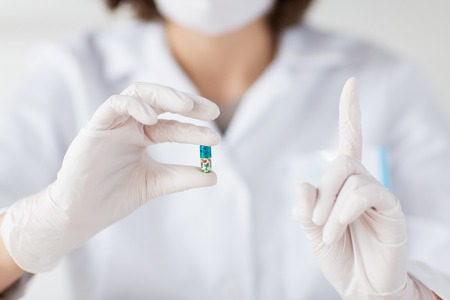 holding close: science, chemistry, biology, medicine and people concept - close up of young female scientist or doctor holding pill and pointing finger up in laboratory