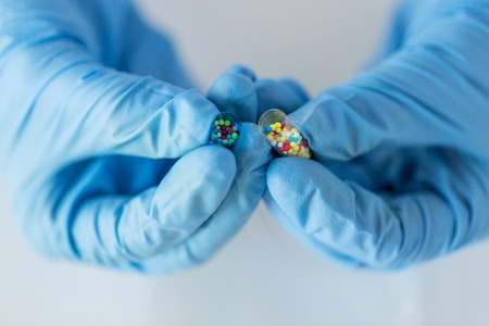 wetenschap, chemie, biologie, geneeskunde en mensen concept - close-up van wetenschapper of arts handen houden en gieten pil inhoud in petrischaaltje in laboratorium Stockfoto